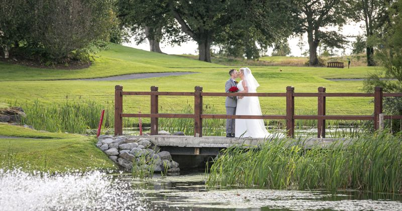Bride and Groom on Bridge by Lake on Golf Course